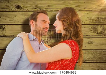 Young couple looking at each other and embracing against blue paint splashed surface