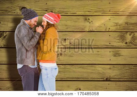 Young couple in warm cloth standing face to face and shivering against blue paint splashed surface