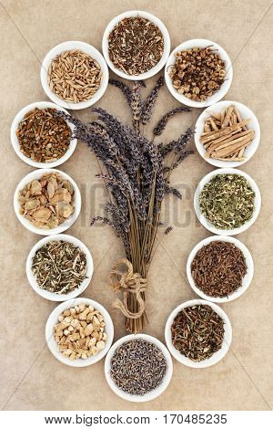 Herb selection for sleeping and anxiety in white china bowls with lavender herb tied in a bunch on natural hemp paper background.
