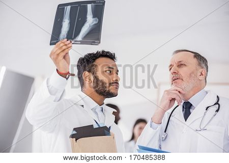 Calm young physician keeping x-ray while situating near colleague in apartment of clinic. Pensive mature male doctor discussing about photo with affiliate