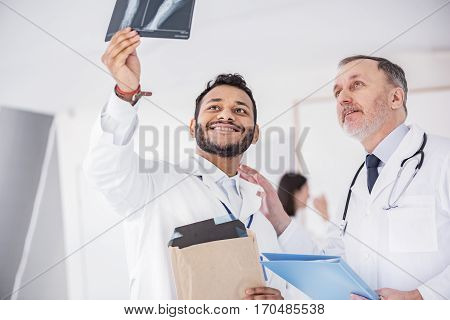 Outgoing therapeutics looking at shadow-photograph while holding it in hand in apartment of clinic. Smiling old doctor keeping paper-folder in his hand