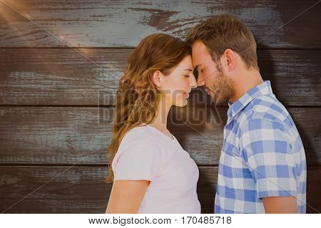 Young couple rubbing nose against wood