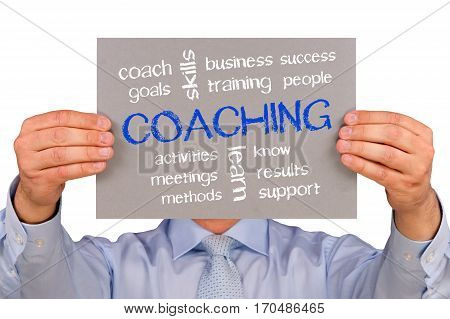 Coaching - Businessman holding sign with text on white background