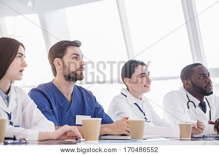 Considerate physicians listening discourse of their partners while sitting at desk at meeting in white apartment of hospital