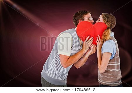 Geeky hipster couple kissing behind heart card against red vignette