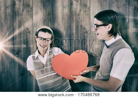 Geeky hipster offering red heart to his girlfriend against pale grey wooden planks