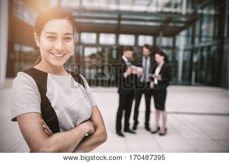 Portrait of confident businesswoman with hands folded in office premises