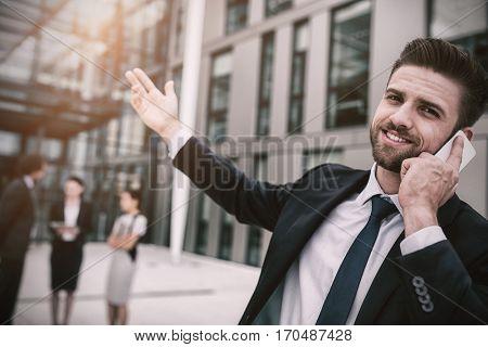 Businessman talking on mobile phone in office premises