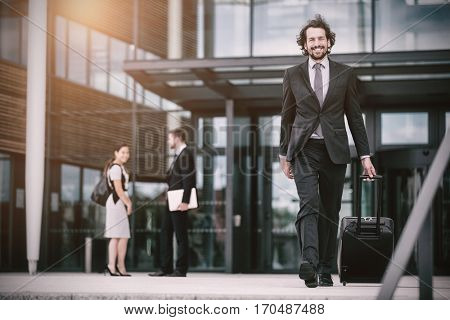 Businessman walking in office premises with suitcase