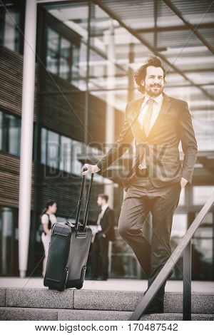 Businessman standing with suitcase at office premises