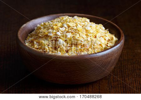 Dry Flaked Corn In Brown Wooden Bowl Isolated On Dark Wood.