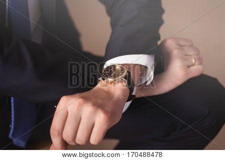 Businessman or Groom look his watch. Closeup.