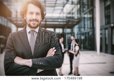 Portrait of confident businessman smiling with arms crossed in office premises