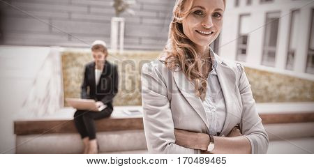 Portrait of businesswoman standing with arms crossed in office premises