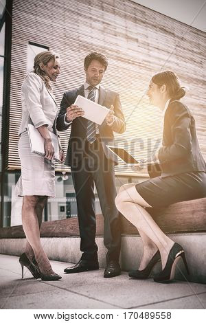 Businesspeople using laptop and digital tablet in office premises