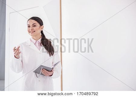 Cheerful doctor asking her colleagues while holding notebook in apartment of clinic