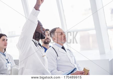 Calm bearded african therapeutic raising hand up while locating with associates at conference in office of hospital