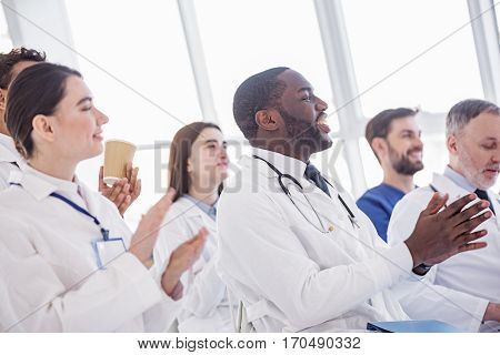 Cheerful male and female physicians applauding their colleagues at the end of his report at conference in office of hospital
