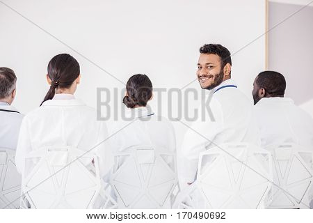 Outgoing bearded physician turning back while sitting near colleagues at conference in hospital room