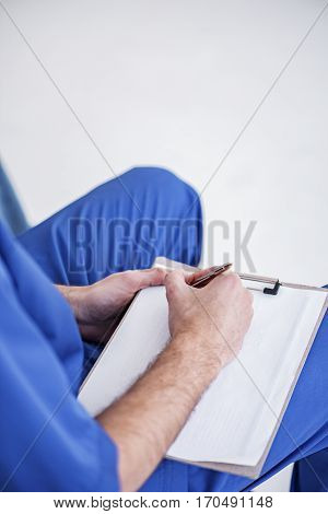 Focus on hands of doctor who making notes of lecture on cardboard panel at conference in room of clinic