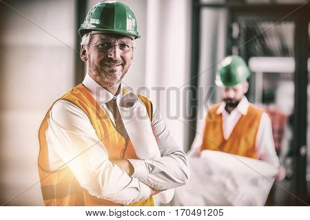 Portrait of architect in hard hat standing with blueprint in office corridor
