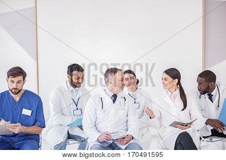 Physicians speaking with each other while sitting in white board during meeting in office of clinic