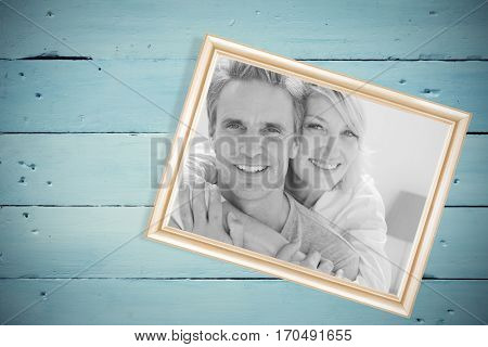 Affectionate couple smiling against painted blue wooden planks