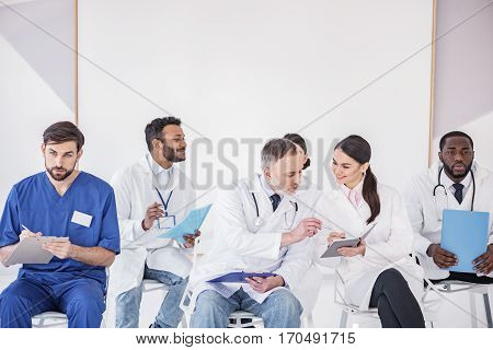 Group of cheerful doctors preparing their reports before conference in apartment of hospital. Attentive old therapeutic looking at notebook of smiling medical adviser in hospital apartment