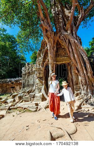 Family visiting ancient Ta Som temple in Angkor Archaeological area in Cambodia