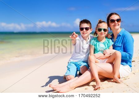 Family of mother and kids on a tropical beach enjoying summer vacation