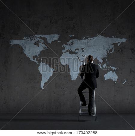Businessman standing on stepladder over world map background. Business, career, progress, concept.