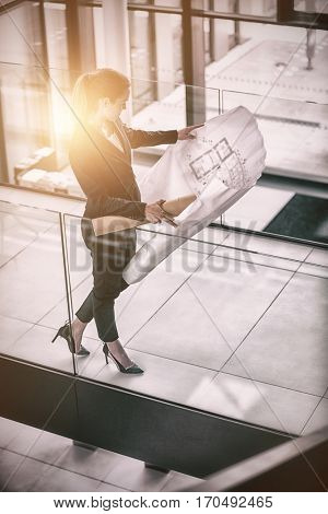 High angle view of businesswoman standing at corridor with blueprint in office