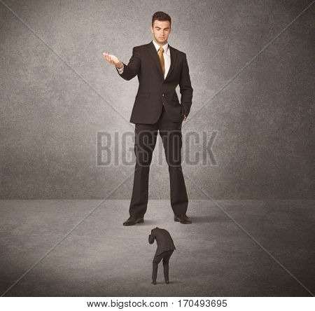 Big business man looking at small worker concept on background