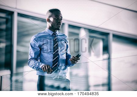 Worried businessman holding mobile phone in hospital