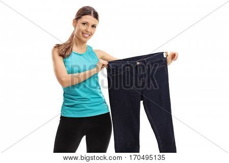 Cheerful woman holding a pair of oversized jeans isolated on white background