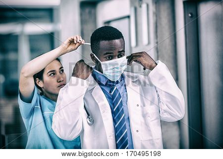 Nurse helping doctor to put on surgical mask in hospital