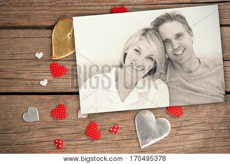 Cheerful couple in bed against smartphone and heart decorations