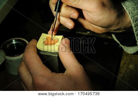 Craft jewelery making. Jeweller creates a wax model of the ring.