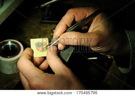 Craft jewelery making. Jeweller is trying on gemstone to the wax model of the ring.