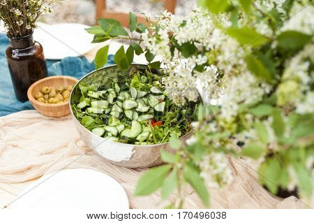 fresh vegetables salad on the served table and a bouquet from spring flowers.