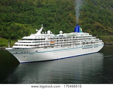 Geiranger, Norway - June 3, 2009: The cruise ship Amadea anchored in Geiranger Fjord in Norway. The tender boats are lowered into the water to take passengers for a shore excursion ashore.