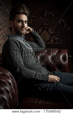 Imposing handsome man in elegant formal clothes sitting on a leather couch. Fashion hair styling, barbershop. Brick wall background. Business style.