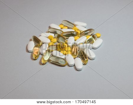 Mixed natural food supplement pills omega 3 calciummagnesium and vitamin B capsules on grey background