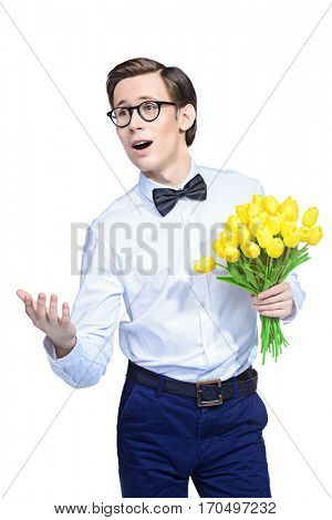 Happy young man in an elegant suit giving a bouquet of yellow tulips. Valentine's Day, Women's Day, Mother's Day. Wedding concept. Isolated over white.