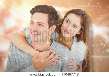 Couple embracing with arms around and looking away against glowing background