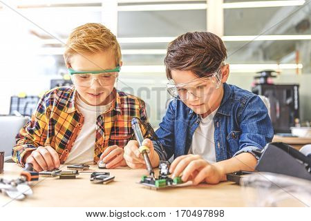 Smiling concentrated boys are sitting near table. They renovating small mainboard
