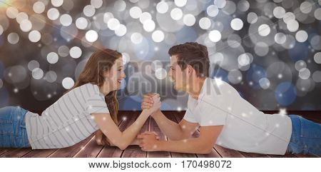 Happy couple arm wrestling against glowing background