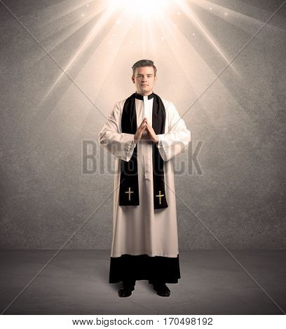 A male religious young priest in black and white dress giving his blessing, holding the holy bible while being illuminated from strong light beams coming from above concept