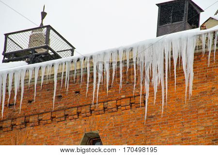 Icicles hanging from roof of red brick house