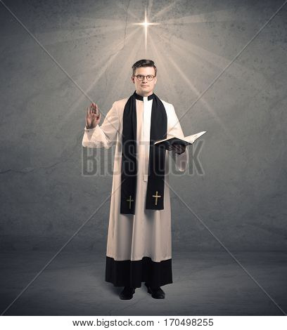 A young male priest in black and white giving his blessing in front of grey wall with glowing cross concept.